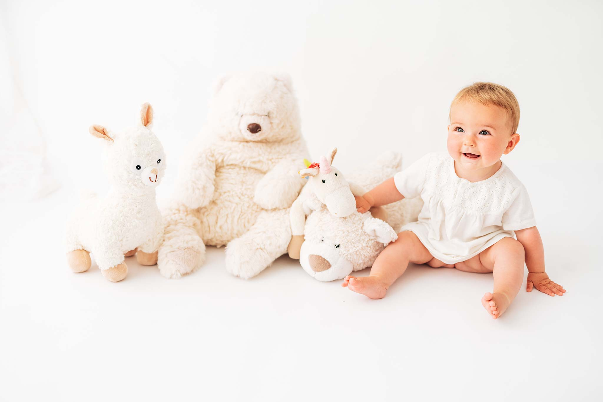 Kinderfotografie München: Baby sitzend mit Stofftieren