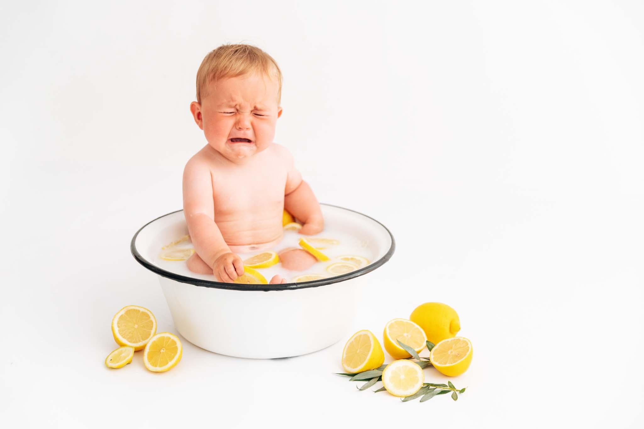 Babyfotograf München: Milchbad-Shooting mit Zitrone , Baby weint